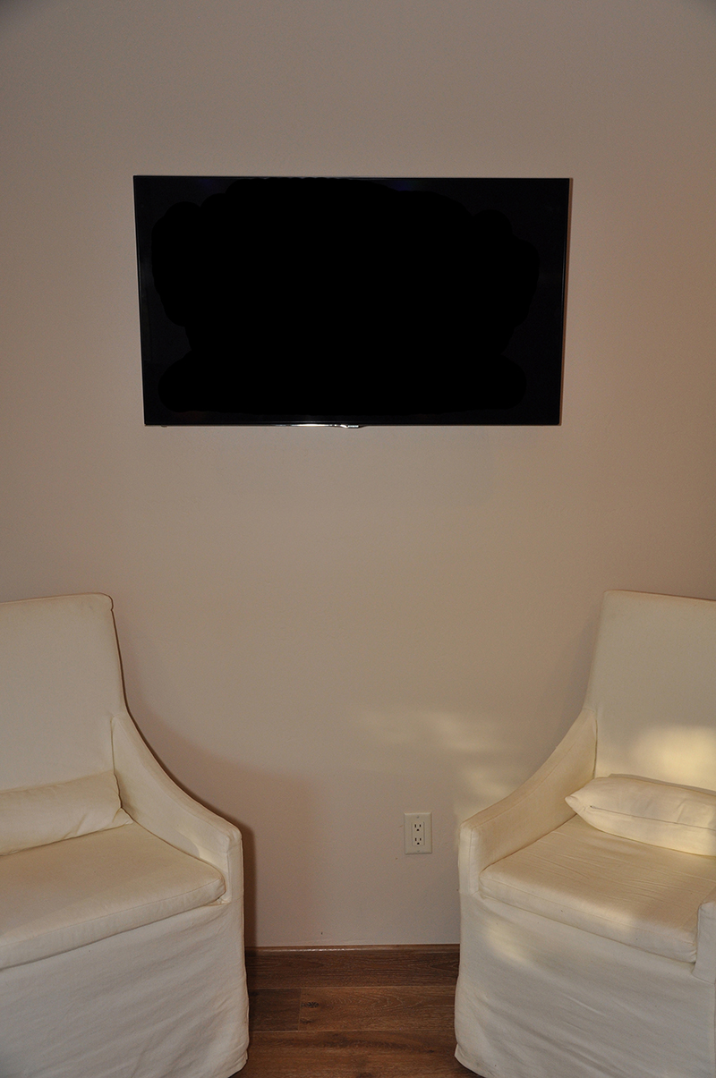 Guest room TV, mounted on the wall, with hidden components behind it, including a wireless access point